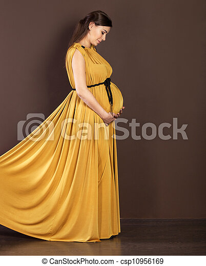 Happy pregnant woman in beautiful long dress - csp10956169