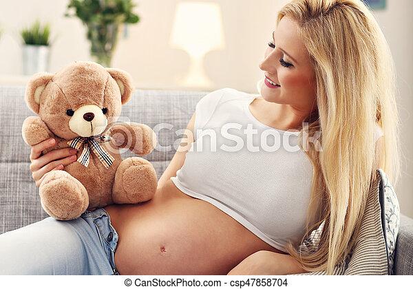 Pregnant woman with teddy bear resting on sofa