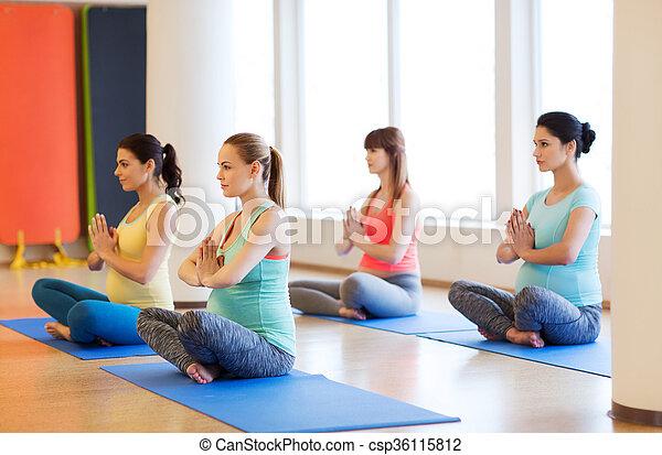 happy pregnant women exercising yoga in gym pregnancy