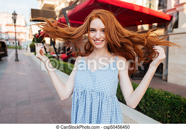 Happy Pretty Redhead Girl With Long Hair Posing While Standing Outdoors On A City Street