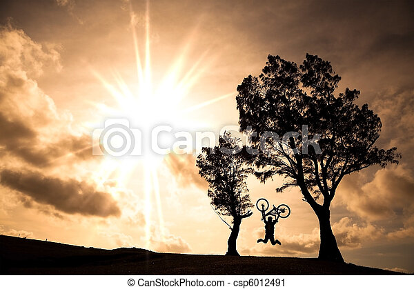 Happy rider holding bicycle and jumping on the hill  - csp6012491