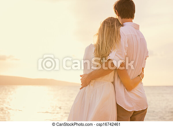 Happy romantic couple on the beach at sunset embracing each other. Man and woman in love watching the sun set into ocean - csp16742461