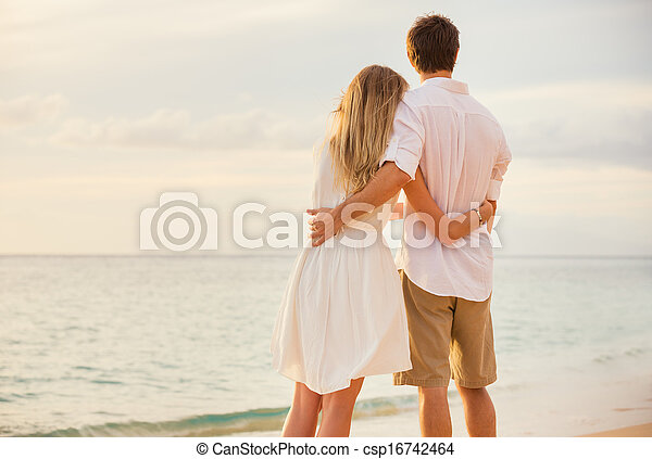 Happy romantic couple on the beach at sunset embracing each other. Man and woman in love watching the sun set into ocean - csp16742464