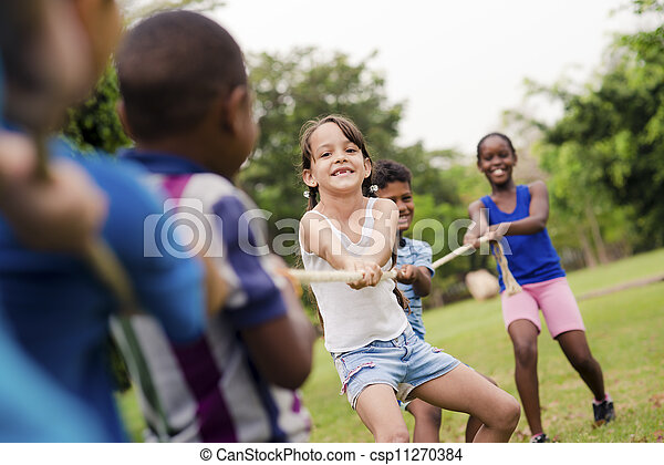 Happy school children playing tug of war with rope in park - csp11270384
