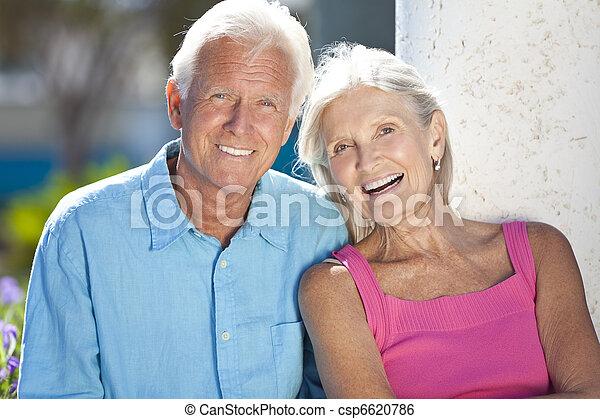 Happy Senior Couple Smiling Outside in Sunshine - csp6620786
