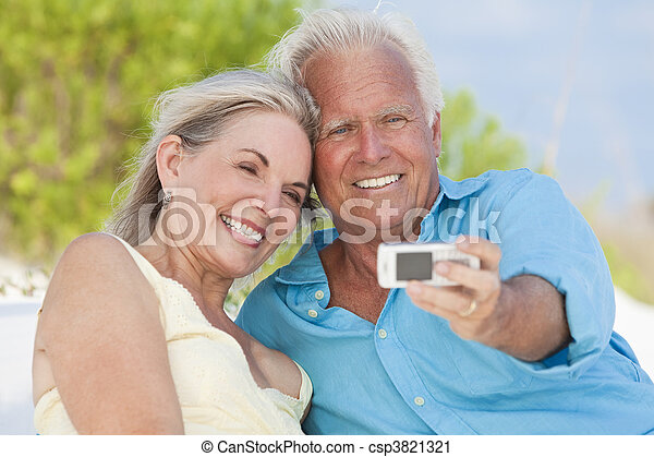 Happy Senior Couple Taking Photographs On Cell Phone At Beach - csp3821321