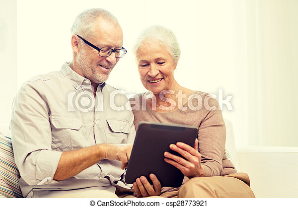 happy senior couple with tablet pc at home - csp28773921