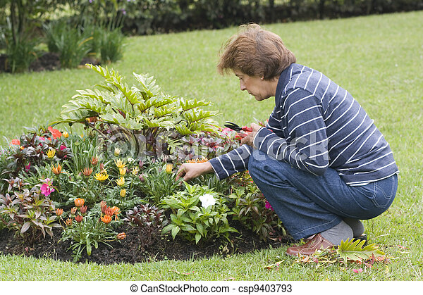 Happy Senior Lady Taking Care Of Her Plants In Garden Outside