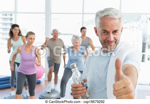 Happy senior man gesturing thumbs up with people exercising in the background at fitness studio - csp18679292