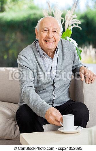 Happy Senior Man Having Coffee At Nursing Home Porch - csp24852895