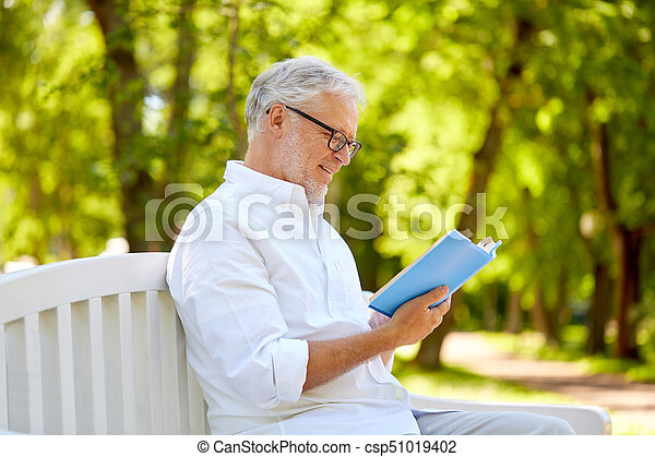 801e148885bc0 Happy senior man reading book at summer park. Old age