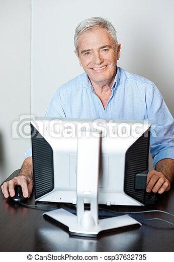 Happy Senior Man Using Computer In Class - csp37632735
