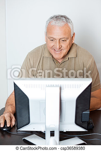 Happy Senior Man Using Computer In Classroom - csp36589380