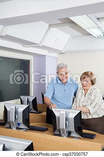 Happy Senior People Using Computer In Classroom - csp37030757