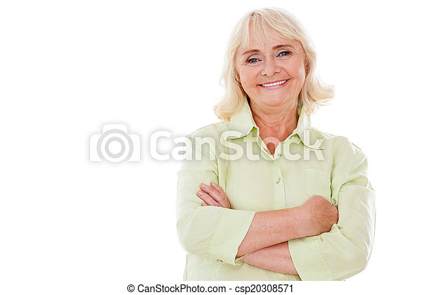 Happy senior woman. Cheerful senior woman keeping arms crossed and smiling while standing isolated on white background - csp20308571