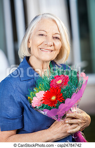 Happy Senior Woman Holding Bouquet At Nursing Home - csp24784742