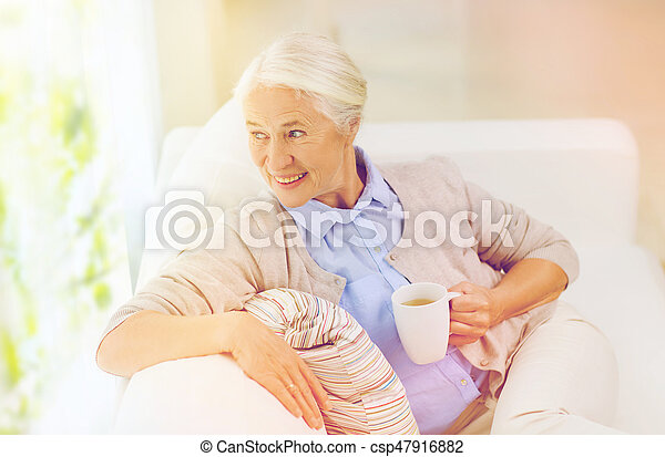 happy senior woman with cup of tea at home - csp47916882