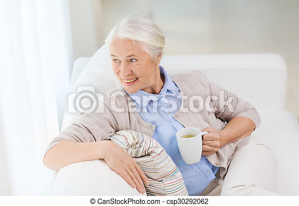 happy senior woman with cup of tea at home - csp30292062