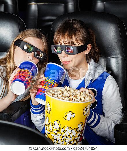 Happy Sisters Having Snacks In 3D Movie Theater - csp24784824