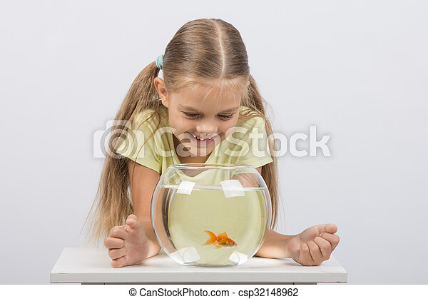 Happy six year old girl looking down on the aquarium with goldfish - csp32148962