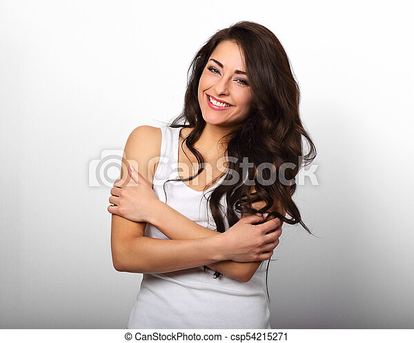 Happy smiling beautiful woman hugging herself with natural emotional enjoying face on white background. Love concept - csp54215271