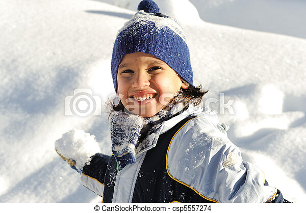 Happy smiling boy throwing snow to you - csp5557274