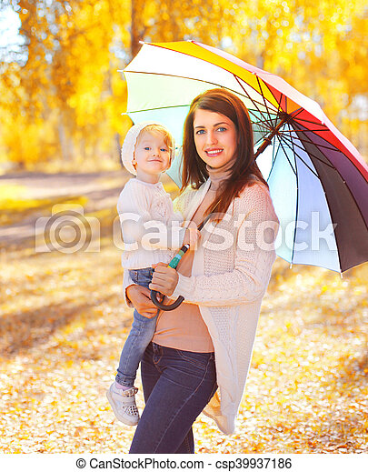 Happy smiling mother and child with umbrella walking in autumn park - csp39937186