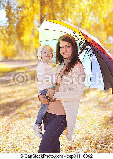 Happy smiling mother and child with umbrella walking in autumn park - csp31118862