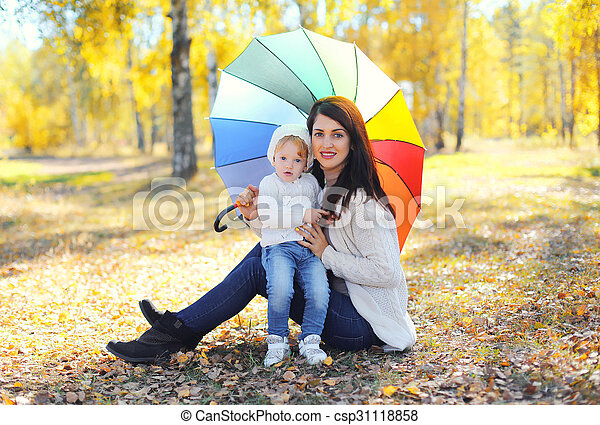 Happy smiling mother and child with umbrella together in autumn park - csp31118858