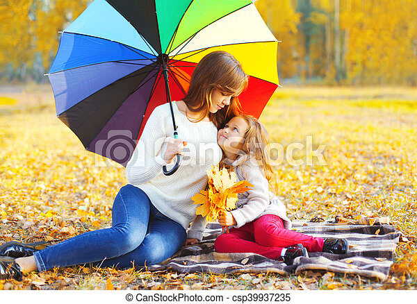 Happy smiling mother and child with umbrella sitting together on the plaid in sunny autumn day - csp39937235