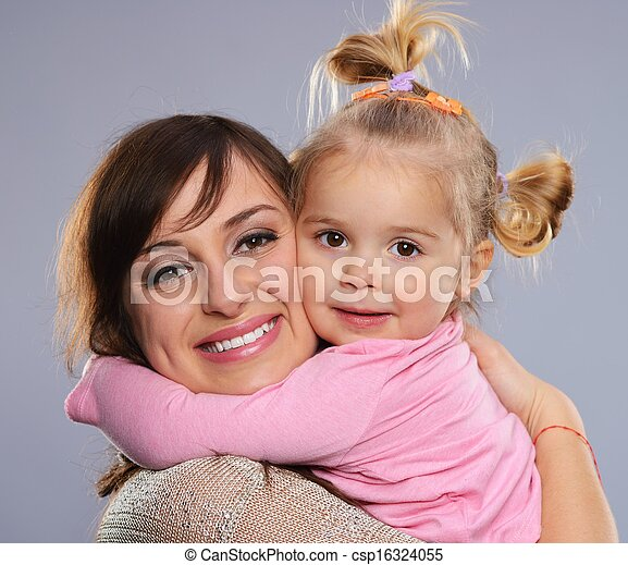 Happy smiling young mother hugs her little daughter - csp16324055