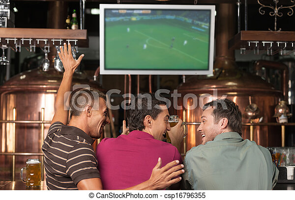 Happy soccer fans. Three happy soccer fans watching a game at the pub - csp16796355