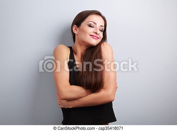 Happy sporty fit woman hugging herself with natural emotional enjoying face. Love concept of yourself  - csp35418071