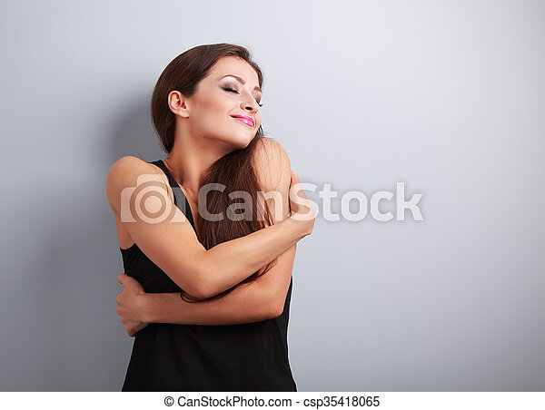 Happy strong sporty woman hugging herself with natural emotional enjoying face  - csp35418065