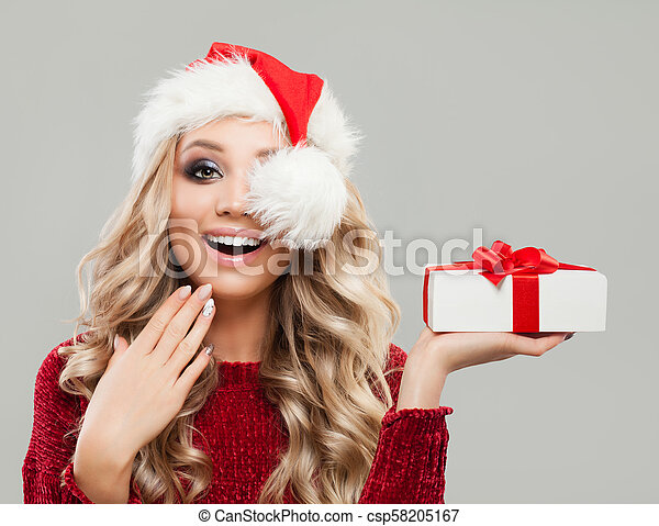 cf3d41527d114 Happy Surprised Christmas Woman Fashion Model holding Christmas Gift.  Smiling Woman in Santa Hat -
