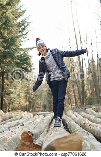 Happy teenage boy having a fun in the autumn forest - csp77061628