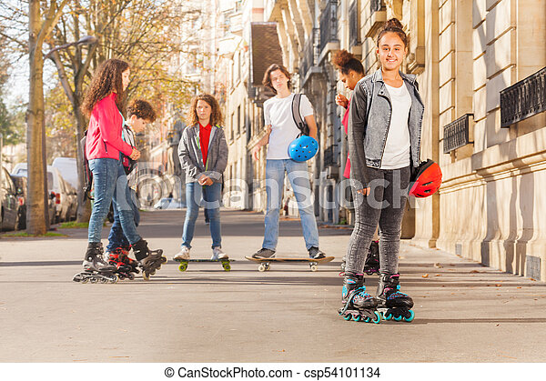 Happy teenage girl in roller skates with friends - csp54101134
