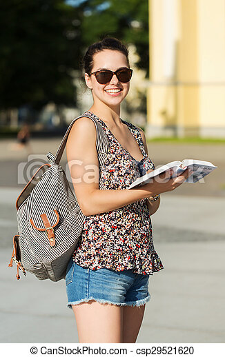 happy teenage girl with guidebook and backpack - csp29521620