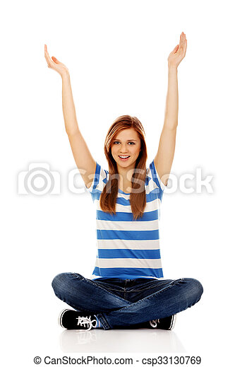 Happy teenage woman sitting with arms up - csp33130769