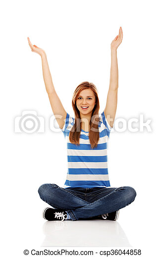 Happy teenage woman sitting with arms up - csp36044858