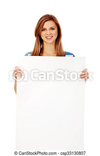 Happy teenage woman with blank billboard - csp33130807