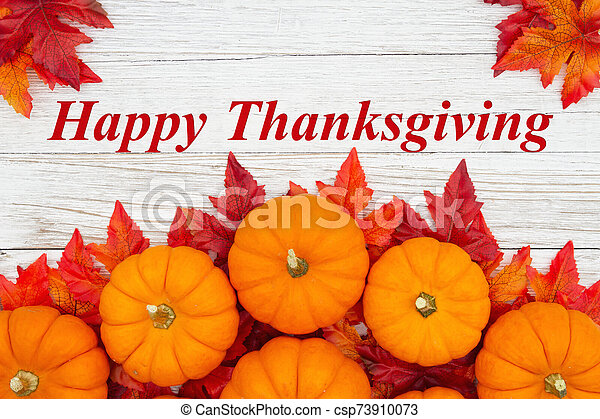 Happy Thanksgiving greeting with red and orange fall leaves and a pumpkins on weathered wood - csp73910073
