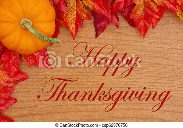 Happy Thanksgiving greeting with red and orange fall leaves and a pumpkin - csp62376756