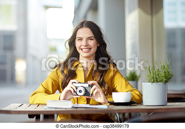 happy tourist woman with camera at city cafe - csp38499179