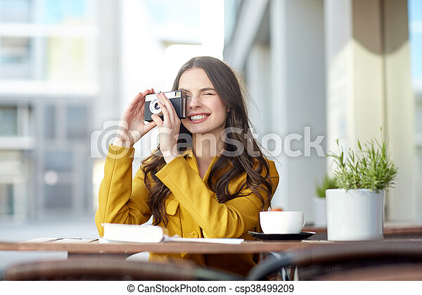 happy tourist woman with camera at city cafe - csp38499209
