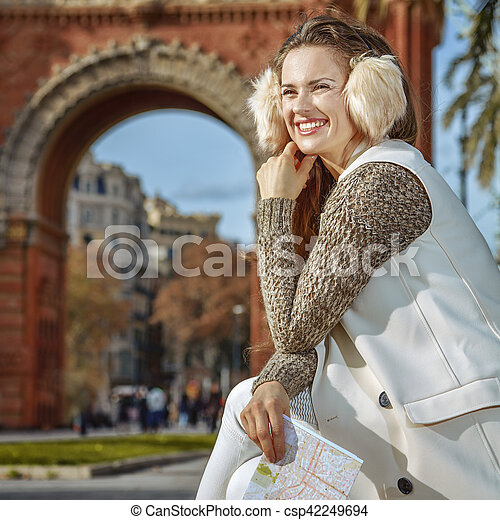 in Barcelona for a perfect winter. happy trendy woman in earmuffs in Barcelona, Spain with map