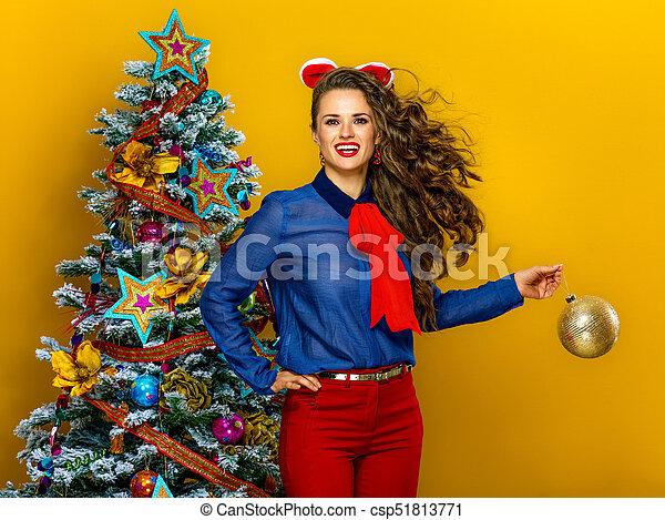 Festive season. happy trendy woman near Christmas tree isolated on yellow background holding Christmas ball