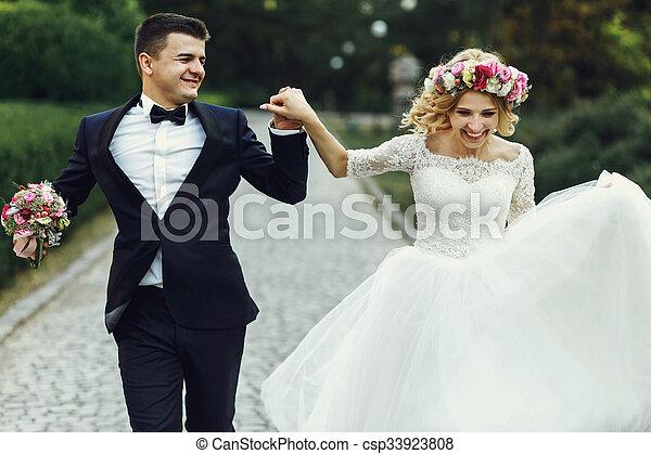 Happy wedding couple charming groom and blonde bride dancing in park - csp33923808