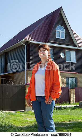 Happy   woman  against her home - csp7698254