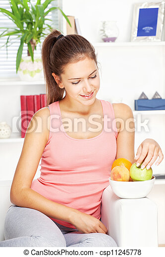 happy woman at home on sofa with fruits - csp11245778